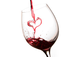 Pouring a heart of red wine in a glass white background